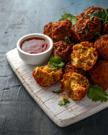 Indian Pakora snack spicy onion, red pepper with chilli sauce on white wooden board