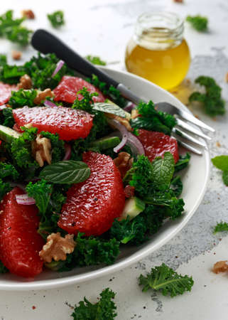Healthy vegan food, vegetarian Grapefruit kale salad with walnuts, red onion and cucumber