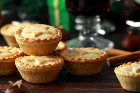 British Christmas mince pies with decoration, gifts, green tree branch on wooden rustic table Stock Photo - 113327401