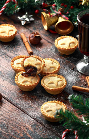 British Christmas mince pies with decoration, gifts, green tree branch on wooden rustic table Stock Photo - 113327402