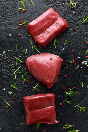 Raw venison steak with rosemary and pepper on black rustic table. Banco de Imagens