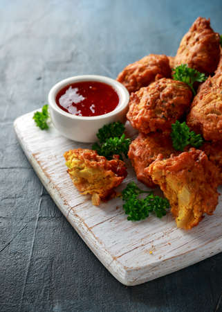 Crispy onion bhajis with sweet chilli sauce on white wooden board