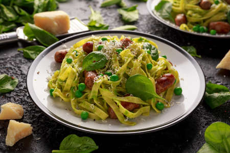 Homemade Pasta with green peas, spinach pesto and sausages. parmesan cheese. healthy food.