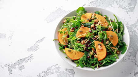 Persimmon and pea shoot salad with walnuts, pomegranate and pumpkin seed in a white table