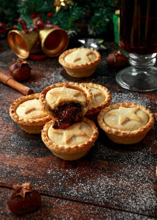British Christmas mince pies with decoration, gifts, green tree branch on wooden rustic table Stock Photo - 114080148
