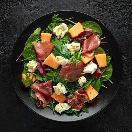 Parma ham and melon salad with mozzarella, green leaves mix Stock Photo