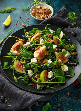Figs salad with blueberries, walnuts, feta cheese and green vegetables. healthy food