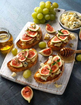 This Fig and Gorgonzola tartines, toast, bruschetta. drizzled with honey on white wooden board Stock Photo