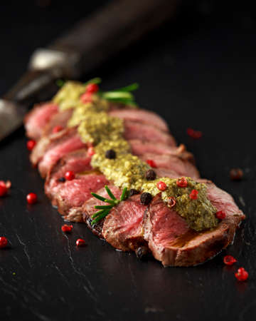 Medium rare venison steak with green pesto sauce and pepper