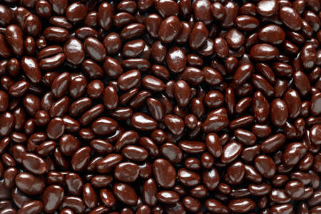 chocolate beans with raisin close up, background, texture.