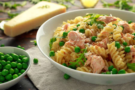 Homemade Pasta fusilli with salmon, green peas, parmesan cheese and lemon. healthy food Imagens