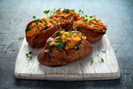 Roast sweet potato stuffed with feta cheese and kale. healthy food Imagens