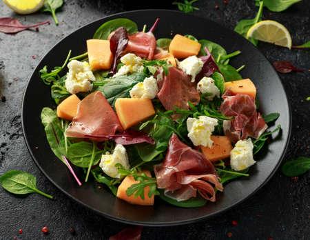Parma ham and melon salad with mozzarella, green leaves mix 写真素材