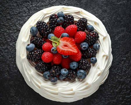 Berry Pavlova cake with fresh blueberries, strawberries and raspberries