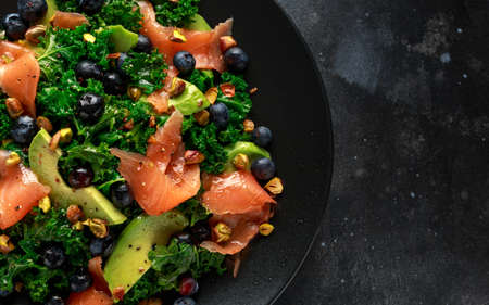 Salmon Kale super food Salad with avocado, pistachio nuts and blueberries on black plate