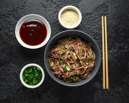 Soba noodles, buckwheat on a black bowl, with spring onion and sesame seeds. Traditional Japanese food.