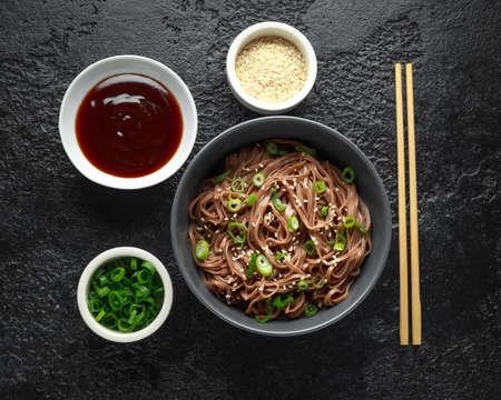 Soba-Nudeln, Buchweizen auf einer schwarzen Schüssel, mit Frühlingszwiebeln und Sesam. Traditionelles japanisches Essen.