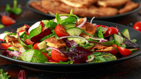Traditional fattoush salad on a plate with pita croutons, cucumber, tomato, red onion, vegetables mix and herbs 스톡 콘텐츠
