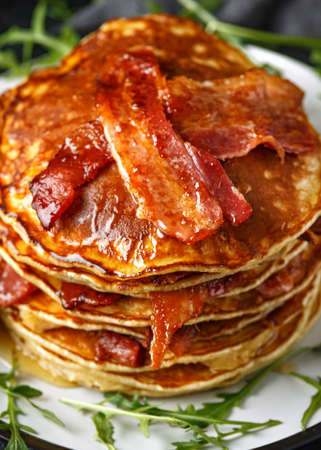 Pancakes with crispy bacon and maple syrup in a plate. Morning Breakfast.