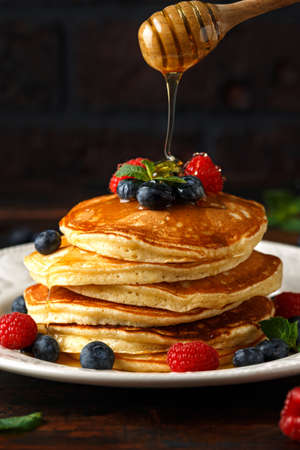 Homemade american pancakes with fresh blueberry, raspberries and honey. Healthy morning breakfast. rustic style. Stockfoto