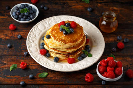 Homemade american pancakes with fresh blueberry, raspberries and honey. Healthy morning breakfast. rustic style.