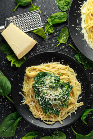 Tagliatelle pasta with spinach in cream sauce with parmesan Imagens