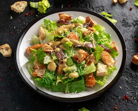 Caesar salad with chicken, anchous fish, croutons, parmesan cheese and greens. healthy food Stock Photo - 117131486