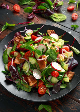 Traditional fattoush salad on a plate with pita croutons, cucumber, tomato, red onion, vegetables mix and herbs Stock Photo