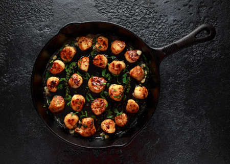 Scallops seared in garlic and parsley butter served in cast iron skillet Stock Photo