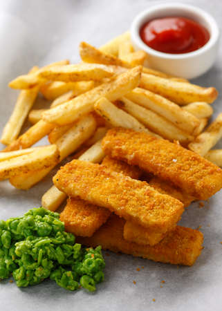 Fish fingers, mashed peas and chips fries. Traditional British fast food. served on crumpled paper Stock Photo