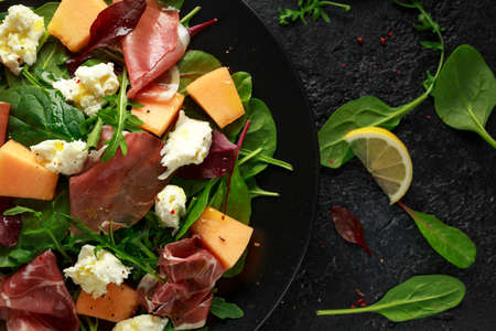 Parma ham and melon salad with mozzarella, green leaves mix Imagens