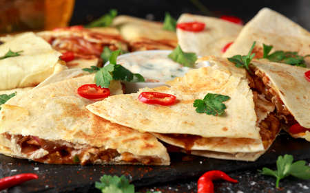 Mexican quesadilla with chicken, cheese and peppers, yogurt dip and chilli. Stock Photo