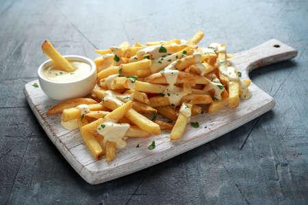 Patatas fritas caseras al horno con salsa de queso sobre placa de madera blanca