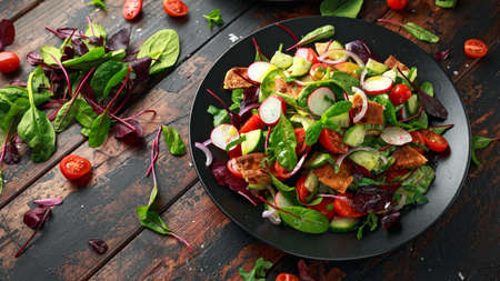 Traditional fattoush salad on a plate with pita croutons, cucumber, tomato, red onion, vegetables mix and herbs Foto de archivo