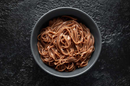 Soba noodles, buckwheat on a black bowl. Traditional Japanese food.