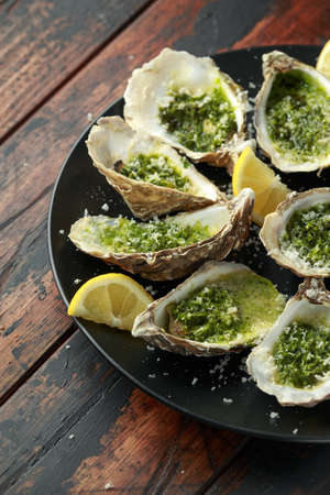 Grilled oysters with Parsley and garlic butter served with parmesan and lemon wedges