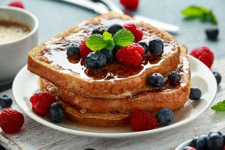Tostada francesa de canela con arándanos, frambuesas, sirope de arce y café. desayuno de la mañana Foto de archivo