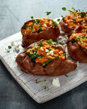 Roast sweet potato stuffed with feta cheese and kale. healthy food Stock Photo