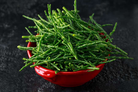 Fresh samphire in a red bowl on black background