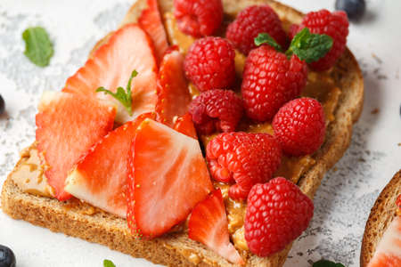 Peanut butter sandwiches with fresh strawberry, blueberry, raspberry and banana whole meal toasts. Stockfoto