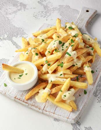 Patate fritte fatte in casa con salsa di formaggio su tavola di legno bianco white Archivio Fotografico