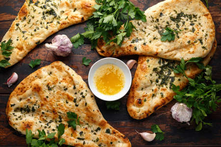 Indian naan bread with garlic butter on wooden table Stock Photo - 118599022