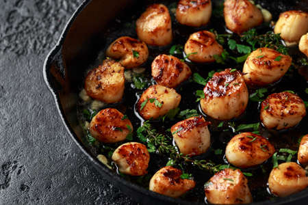 Scallops seared in garlic and parsley butter served in cast iron skillet Reklamní fotografie