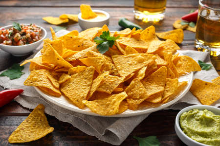 Tortilla nachos chips with cheese sauce, guacamole and tomatoes salsa dip. glass of beer. Banque d'images - 118599208