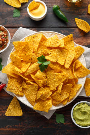 Tortilla nachos chips with cheese sauce, guacamole and tomatoes salsa dip. lime. chilli pepper. 免版税图像 - 119118836
