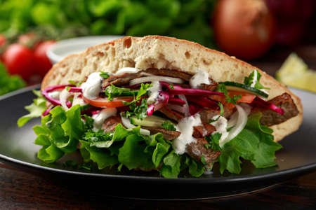 Doner kebab, fried lamb meat with vegetables and garlic sauce in turkish bread Archivio Fotografico - 119118861