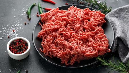 Carne picada fresca cruda, carne picada, carne molida con hierbas y especias en placa negra Foto de archivo
