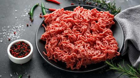 Vers Rauw gehakt, Rundergehakt, gemalen vlees met kruiden en specerijen op zwarte plaat Stockfoto