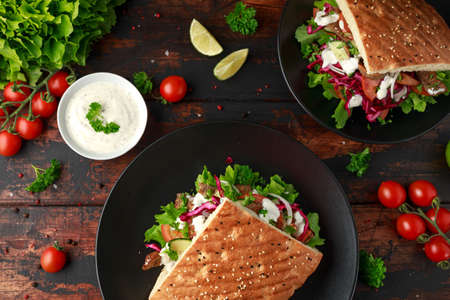 Doner kebab, fried lamb meat with vegetables and garlic sauce in turkish bread Archivio Fotografico - 119397377