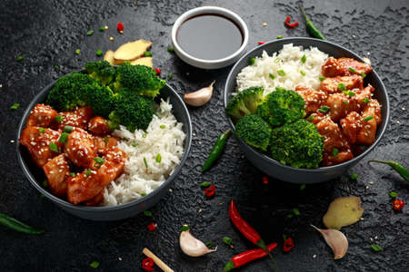 Teriyaki chicken, steamed broccoli and basmati rice served in two Asian clay bowls Foto de archivo - 119397949
